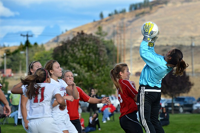 Omak's goalkeeper Trisha Priest goes up high for soccer ball during match with Okanogan on Thursday. The Bulldogs won, 4-0, in the non-league match.