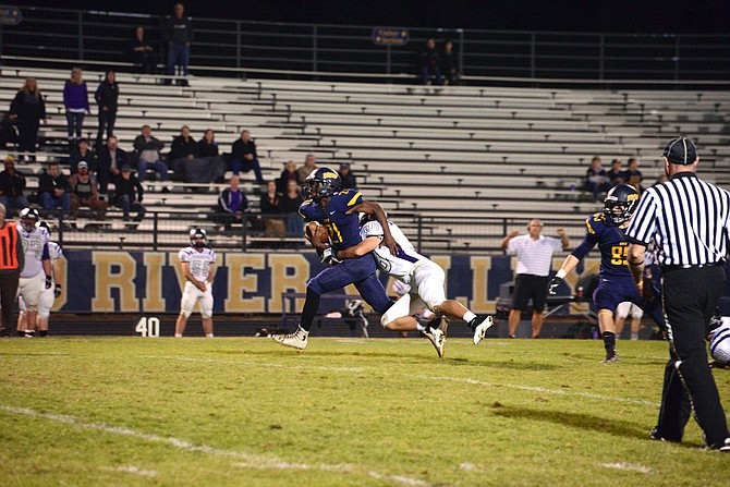 MICHAEL JONES (No. 21) drags a Ridgeview tackle during one of his 12 carries in Friday's game. The sophomore back racked up 57 yards on the ground.