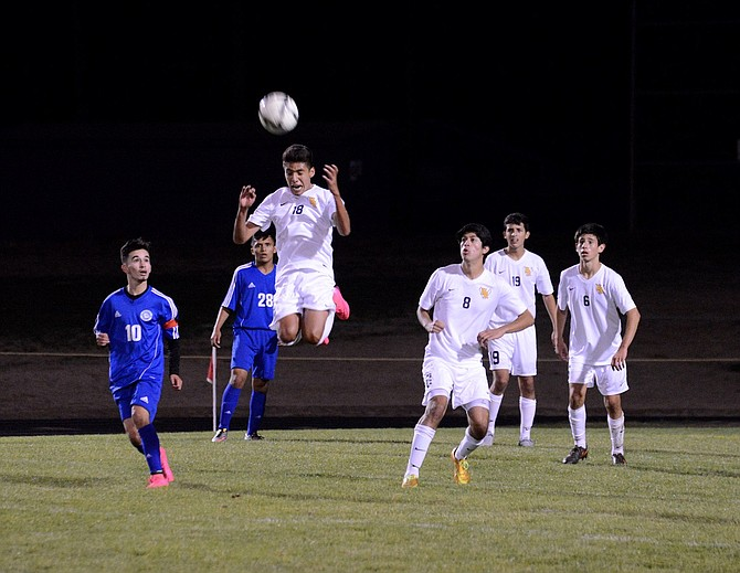ANDRES BAEZA gets his head in the game in the second half, while his teammates Carlos Marquez, Emy Gutierrez, and Orlando DeLaTorre look on.