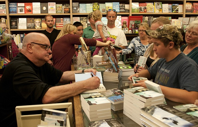 "STEVEN KLAVITER was first in a long line to get copies of ""Peak"" and ""The Edge"" signed by author Roland Smith Tuesday night at Klindt's Booksellers in The Dalles."