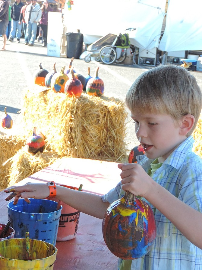 Harvest Festival highlights include large pumpkin carving — and pumpkin painting (right) in the Kids' Zone.