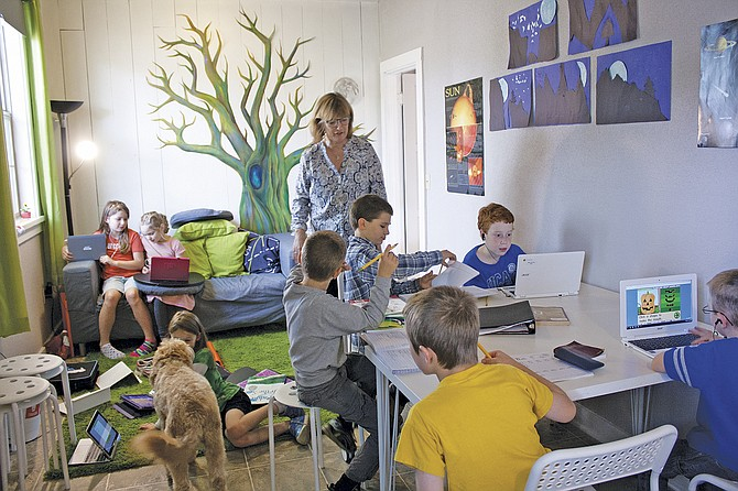 Dallas Community School is in its third school year. The charter school was founded to provide families of home-schooled students support for curriculum and help with instruction. Here, Julie Rain assists students working on projects when the school opened in 2015.