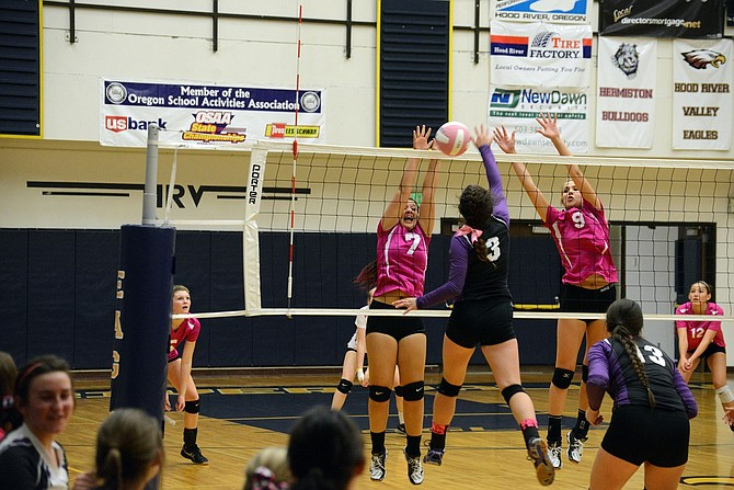 KAYLIN WINANS (left No. 7) goes up for a block with teammate Katie Kennedy (No. 9) during Thursday night's game against Hermiston.