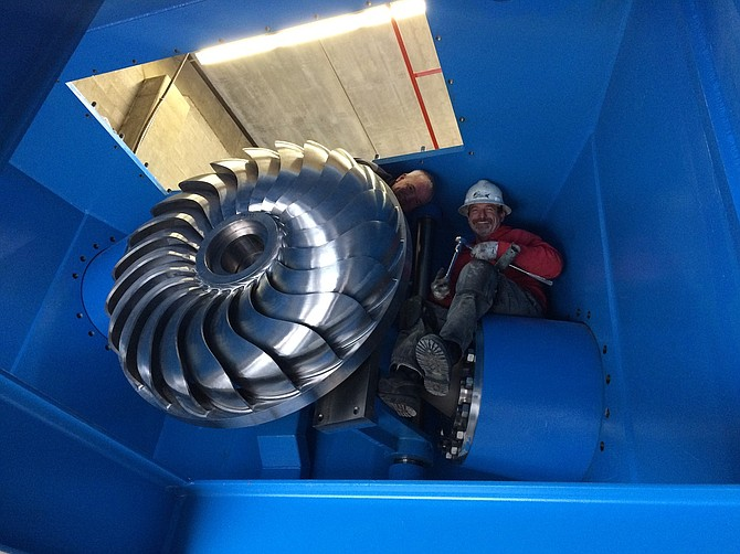 DAVID MORRIS of Gilkes Construction and Jerry Hudson of Crestline Construction install a new turbine and generator at Farmers Irrigation District's hydropower plant. Gilkes manufactured the turbine and Crestline installed the machinery.