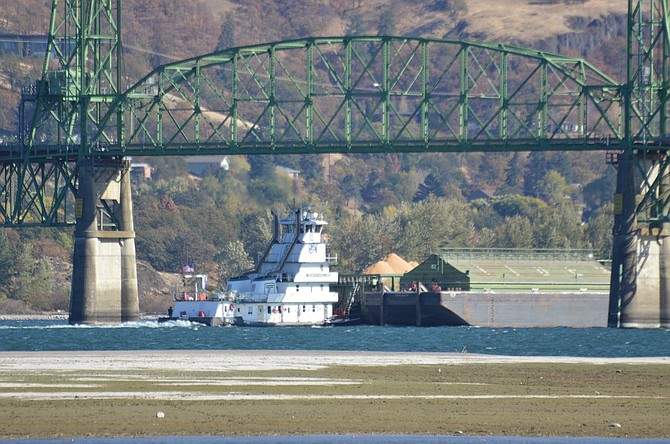 A BARGE sails under the Hood River Bridge, passing the site where an unknown vessel struck the north pier earlier this month. The port is assessing damages and investigating the cause of the two scrapes, which mark the support pillar on its east face and west corner.