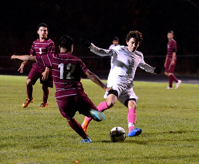 NOE MAGANA (white jersey) gets in position to block a shot from The Dalles' Brandon Bustamante during Tuesday night's game against the Riverhawks at Henderson Community Stadium. Magana scored the first goal for the Eagles, who would go on to beat The Dalles, 3-0. HRV will face a to-be-determined playoff opponent Tuesday, Nov. 3 in Hood River.