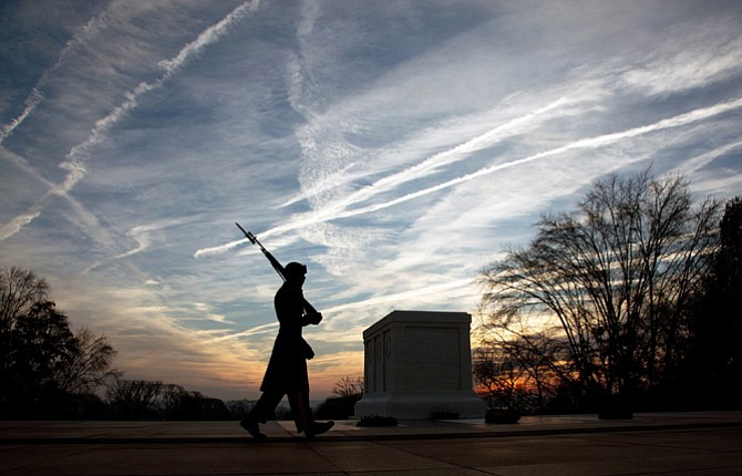 "A SENTINEL at Arlington National Cemetery in Virginia walks the mat in front of the Tomb of the Unknown Soldier as dawn breaks. The Tomb Guards have been on duty around the clock to guard the crypt since 1937. Their motto is: ""Soldiers never die until they are forgotten, tomb guards never forget."" 	Contributed photo"