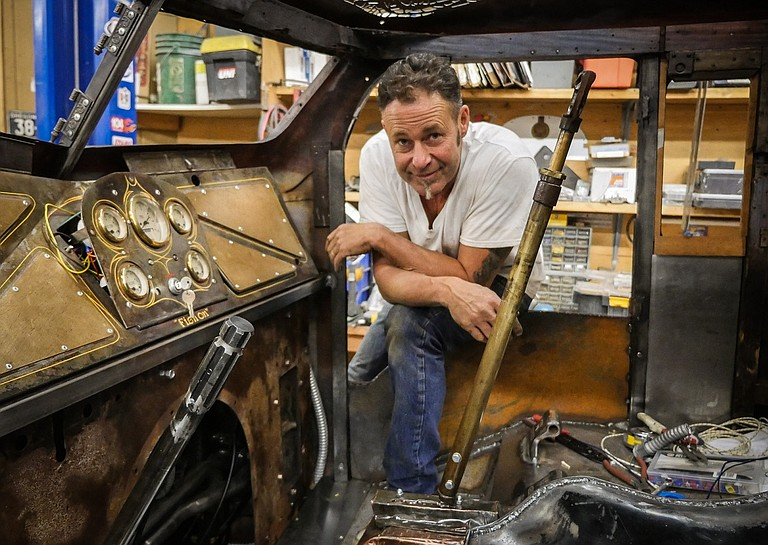 RESURGENCE build chief Gary Fisher looks through the rat rod cap, with its intricate hand-done metal cutting by Kelly Phipps.
