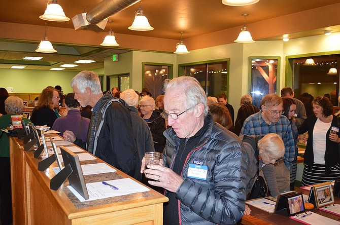 MULLING his silent auction choices is Jean Michel Bock of Hood River at Warm The Night, the Nov. 7 auction fundraiser for the Hood River Warming Shelter, at its new location, the former Fruit Tree Building on Westcliff.
