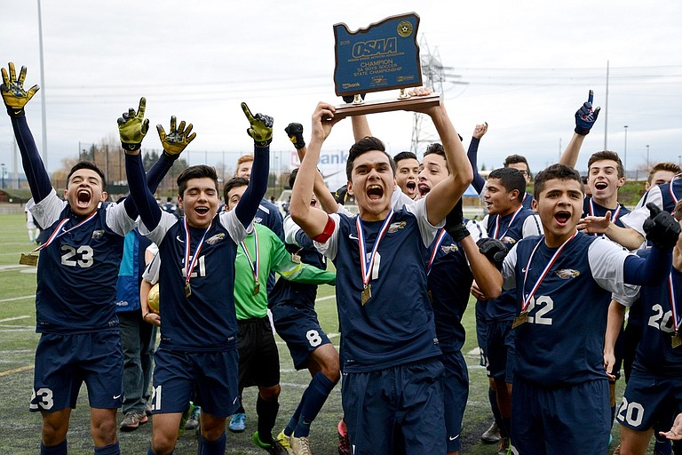 THE HRV BOYS SOCCER TEAM celebrates while captain Mario Sandoval hoists the OSAA 5A state championship trophy into the air following Saturday's title game. The Eagles defeated the Wilsonville Wildcats, 2-0, at Hillsboro Stadium this past Saturday to claim their second consecutive 5A title.