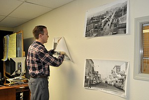 MATTHEWKLEBES, director of The Dalles Main Street program, puts historic images up on the walls of his new office.