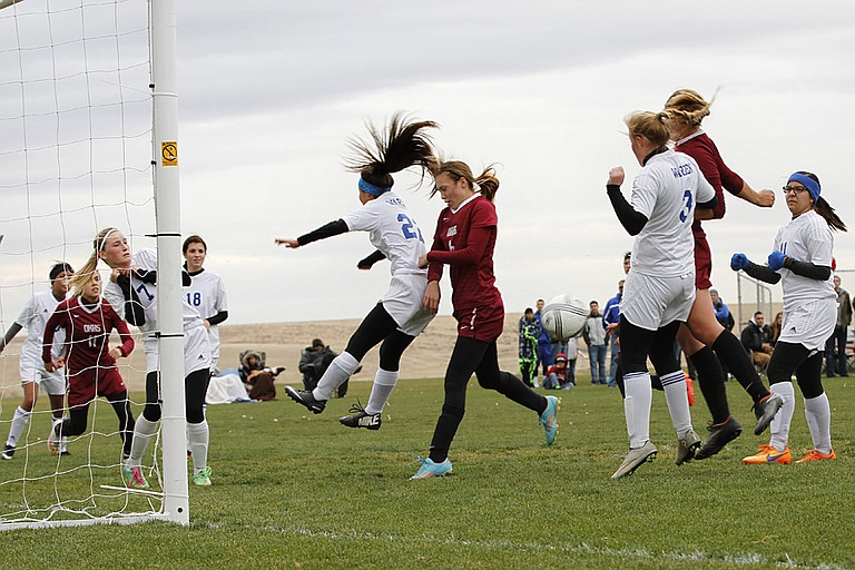 Okanogan players work the Warden goalkeeper box during state quarterfinals. The Bulldogs open state soccer play Friday against Adna.