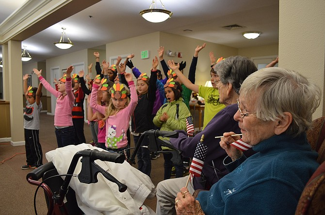 """Thanksgiving Gifts: Students from Mid Columbia Adventist School visit Parkhurst Place on Monday to wish residents a """"Happy Thanksgiving"""" in song. Students presented residents with flags, to go with their finale, """"God Bless America,"""" and Peggy Briggs and Kathleen Nichols, far right, join other residents in singing along."""