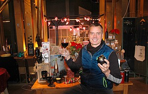 JAMES MARTIN raises a toast, and a Christmas ornament, in front of a holiday-themed display of merchandise at Sunshine Mill Winery downtown The Dalles. Housed in a historic flour mill, the large building has unique challenges when it comes time to light the exterior, Martin said.