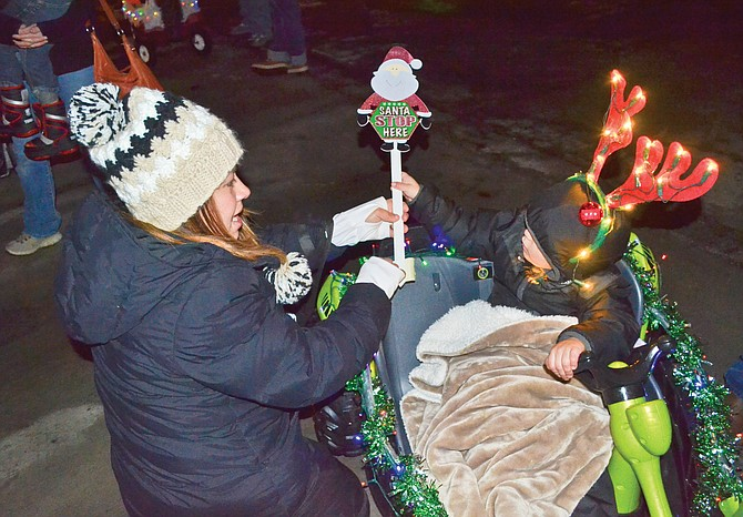 Kacey Soto helps her son, Jaycek Soto, with last-minute preparations before the second-annual Kids Lighted Christmas Parade began. See Page A8 for more coverage.