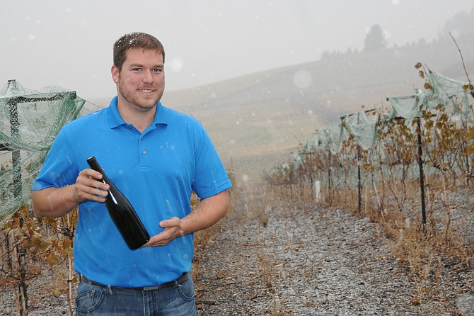 Brent Uhlorn holds a bottle of wine made from this fall's Riesling grapes on a snowy November day.