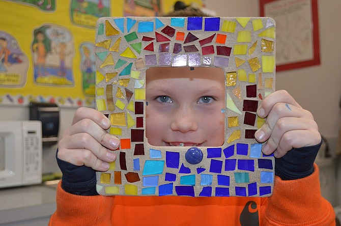 Jess Aubert of Parkdale peers through a class project picture frame (a classmate's, as his was already wrapped).