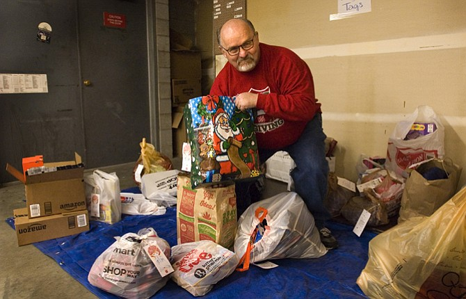 SALVATON ARMY Major Ron Wildman stands among gifts donated through the Angel Tree program in The Dalles. Gift returns are down almost 80 percent, with a Friday deadline for gifts.