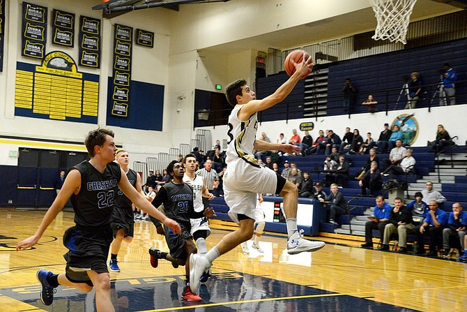 HEARTS were broken Tuesday night, as HRV fought hard against the 6A Gresham Gophers, but lost thanks to a three-point shot suck by the Gophers with just two seconds remaining. Noah Noteboom (white jersey) sprints past Gresham defenders on his way to a layup.