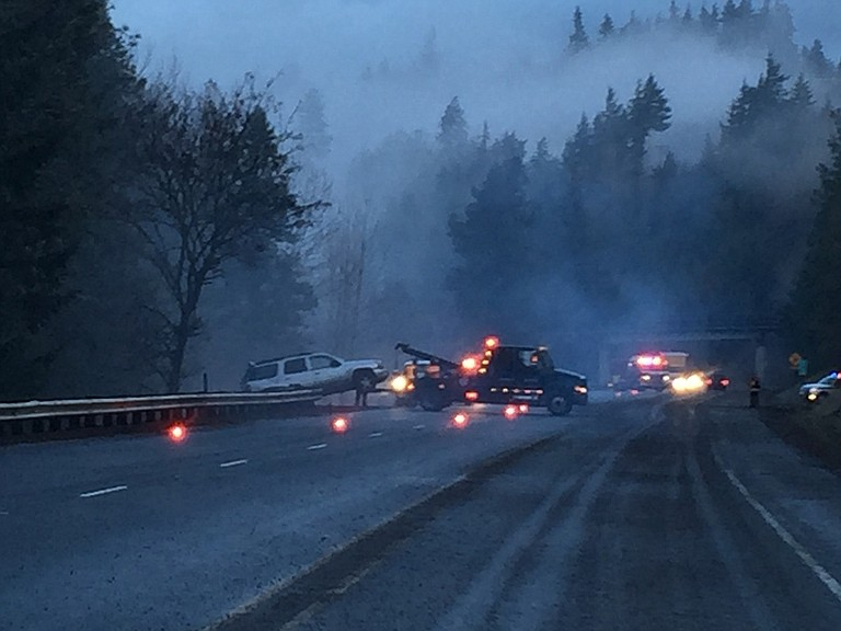 LAW ENFORCEMENT and fire agencies responded to multiple vehicle problems on icy Highway 35, including this SUV up over the guardrail, southbound near Whiskey Creek. Displaced gravel caused by skidding cars is visible at right. ODOT dispatched de-icers to improve travel safety.