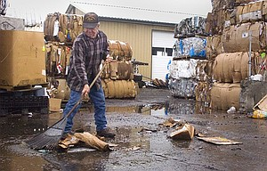 PAUL LEPINSKI, owner of A&P Recycling in The Dalles, rakes up trash and pieces of cardboard Monday afternoon as he cleans up his recycling area. More recycling was waiting to be shipped than usual due to the brief closure of Interstate 5 due to flooding and snow in the Columbia River Gorge.