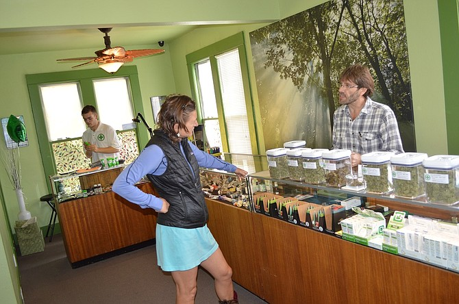 MIKE RACHFORD, right, owner of the Gorge Green Cross on Oak Street, discusses marijuana strains with Isa Silver of Hood River in October, when local dispensaries first began selling cannabis to retail customers through the state's early sales program. On Jan. 4, a 25-percent tax kicked in on retail marijuana, and dispensaries such as the Green Cross are applying for a license to continue recreational sales.