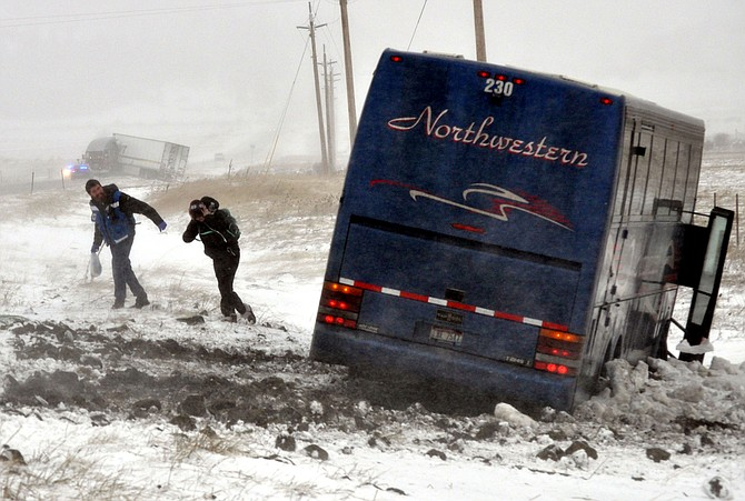 A Syringa Ambulance EMT assists a passenger up the slippery snow-covered slope along U.S. Highway 95 where a Northwestern charter bus was blown off the road Saturday morning, Jan. 16. One minor injury was reported.