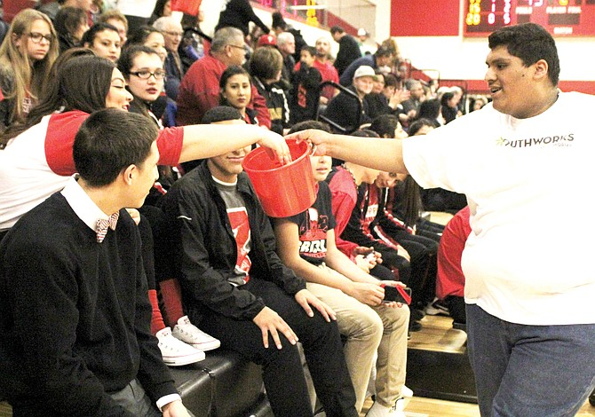 Mr. SHS candidate Gerardo Martinez collects money from fans during a break in the action of Friday's Grizzlies basketball game. Candidates are raising money to benefit Children's Village.