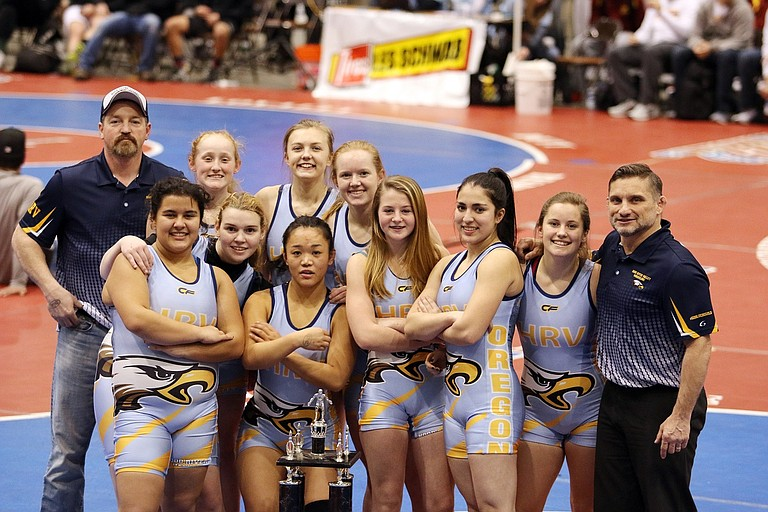 THE UNDEFEATED EAGLES pose in their new singlets with their new trophy after crushing Elmira High School, 76-0, sweeping the team in 13 matches — all of which ended in pins.