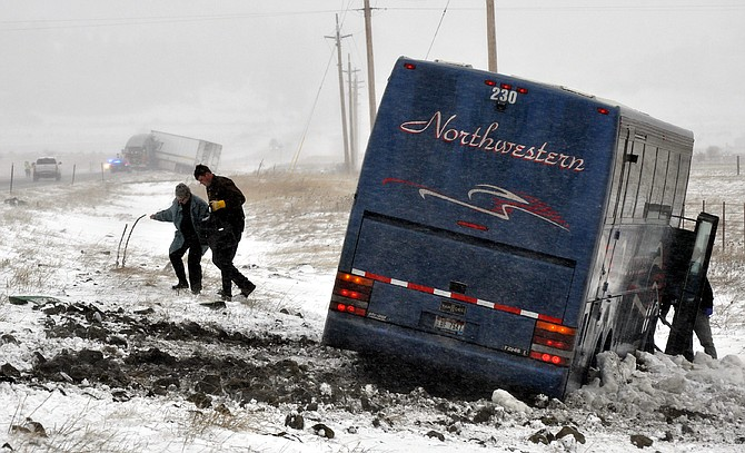 A member of the Grangeville Rural Fire Department helps a bus passenger up the slippery slope at last Saturday's slideoff accident south of town on U.S. Highway 95. High winds and slick conditions contributed to four accidents that Jan. 16 morning.