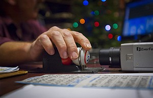 Gary Patton rotates a randomly-drawn ball in front of a video camera so that it is displayed on monitors throughout the dining room at Mid-Columbia Senior Center during a bingo game Thursday. Games are held at the center Thursday and Saturday nights.