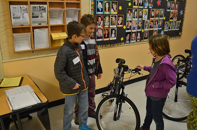 """May Street students, from left, Sawyer Clemett, 9, Massimo Blanco, 10, and Stella Lee, 10, admire the bikes donated by Immanuel Lutheran's senior high youth group. """"They're really cool!"""" Blanco said."""