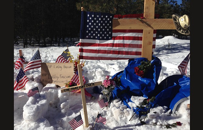 A makeshift roadside memorial for rancher LaVoy Finicum stands on a highway north of Burns Jan. 31. Finicum was killed last week in a confrontation with the FBI and Oregon State Police on a remote road. Four people occupying the Malheur National Wildlife Refuge held their position Sunday. They have demanded that they be allowed to leave without being arrested.