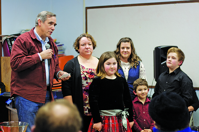 Sen. Jeff Merkley, left, talks about Faces before present director Amy Houghtaling with a flag Friday in Falls City.