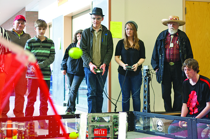 Adam McCombs, second from right, and Grace Valdez, right, from Lakewood, Wash. driver their team's robots in the championship round of Saturday's Dallas Robotics Tournament at Dallas High School. McCombs and Valdez were on the winning alliance in the final round of the event, which drew more than 30 teams from Oregon and Washington.