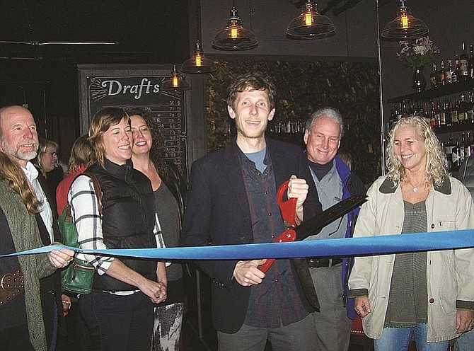 Surrounded by a large crowd, Tarwater Tavern owner Nick Baldridge cuts the official Mt. Adams Chamber ribbon during the pub's grand opening Friday night. Tarwater is open seven days a week, starting at 5 p.m. It serves a wide selection of regional beers, wines, and alcohol.