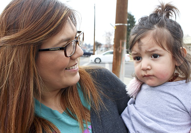 """Melissa Sarmiento and her 18-month-old daughter Mila were among the faithful taking advantage of the """"Ashes on the Go"""" Wednesday at the corner of South Ninth Street and East Edison Avenue. Ashen crosses were painted on their foreheads by Pastors Katrina Walther and Pat Beeman, who have offered the Ash Wednesday services for the past several years."""