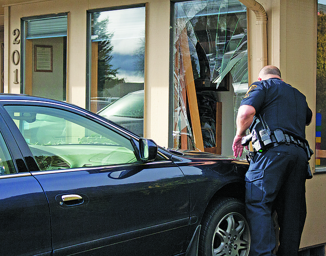 Dallas Police Office Colby Hamilton takes photos of a car verses building crash in Dallas on Monday morning. No one was injured in the accident.