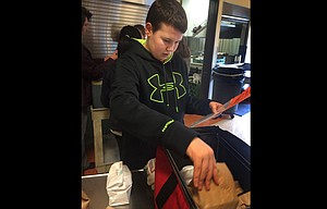 St. Mary's Academy eighth grader Jake Dollarhide checks to make sure all the food prepared for his Meals on Wheels route is accurate for the dietary needs of the 14 meal recipients.
