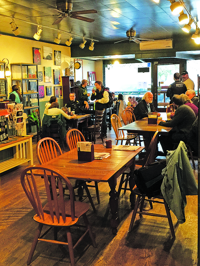 People enjoy a cup of coffee during the Coffee with a Cop on Friday afternoon at Rick's Place in Monmouth. The event was aimed at breaking down barriers between police officers and the citizens they serve.