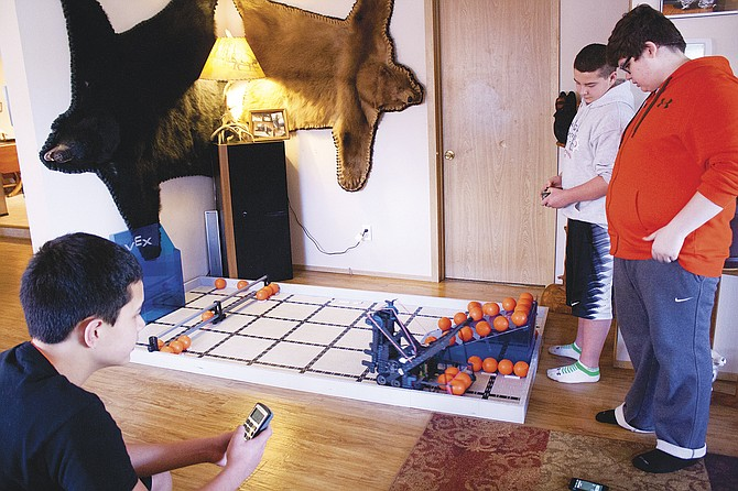 Ryan Nguyen, left, keeps time as teammates Kahl Murdock and Gavin Boyson take turns driving their robot during a practice on Monday afternoon. The LaCreole Middle School trio is headed for Vex Robotics IQ World Championships.