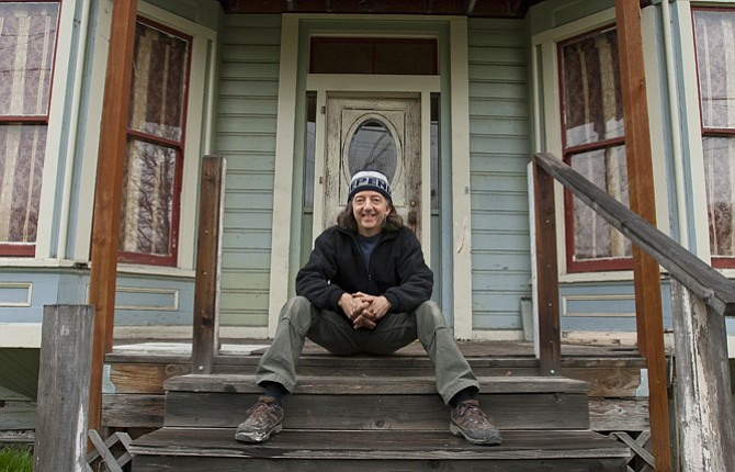 Local musician Victor Johnson sits on the porch of the Herbring House, a Civil War era building he hopes to restore located near Saint Peters Landmark downtown The Dalles.