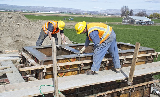 Tyler Leighty and Dana Schilperoort put the finishing touches on a cement weir box at Snipes Canal in Outlook.