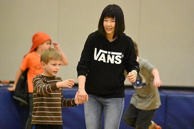 Ethan Ready, 8, guides Sayaka Ono at skate night.