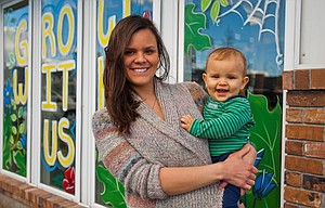 Maria Mueske, co-owner of The Twisted Vine Garden Center in The Dalles with her partner Cole Griffiths, holds their son Forrest outside their store on Second Street. Although the store caters heavily to marijuana growers, Mueske, who studied horticulture and botany, hopes to serve gardeners of all types.