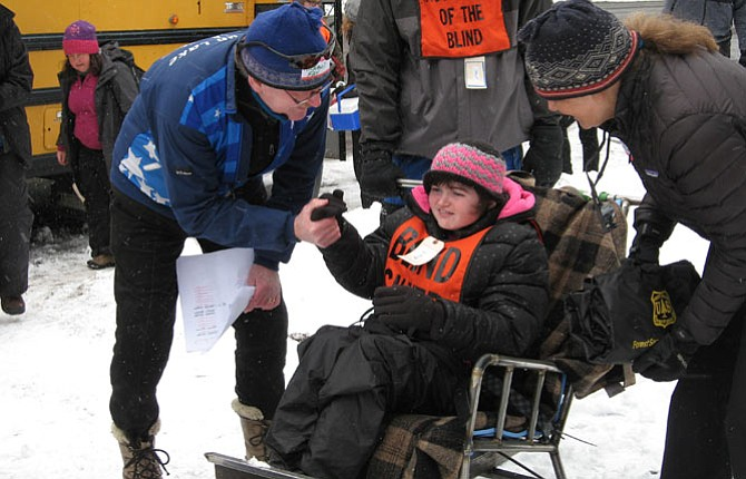 "Richard Fay and Shelly Hakanson greet Ella Trout as she is introduced to a ""sit-ski"" created for her use at the Teacup Nordic Center on Mount Hood. Ellas is a student at Washington State School for the Blind.