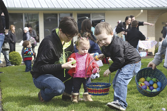 Donna Compton, left, helps Lydia Nightengale, 1, hunt for eggs, while Jace McKibben, 4, races ahead. The Easter Egg Hunt at Jefferson Lodge was one of numerous local egg hunts over the weekend.