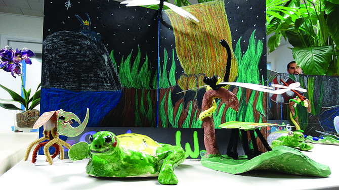 Sadie Welborn's turtle takes a step in her diorama of the cloud forest, surrounded by a damselfly and Hercules beetle. In the background, a jungle cat takes a step.