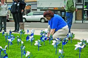Heather Smith, early learning and family engagement coordinator, plants a blue pinwheel at the Polk County Courthouse in honor of Child Abuse Prevention Month on Monday.