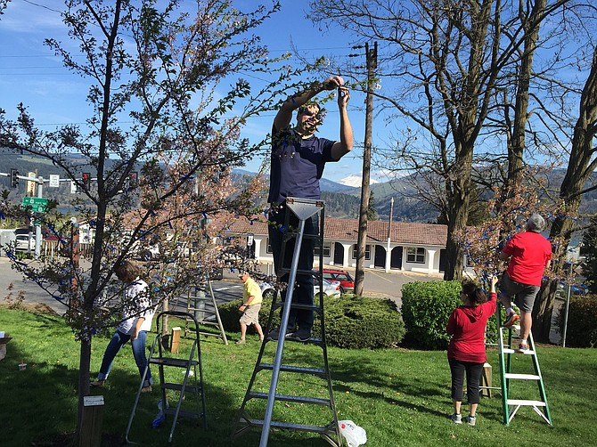 AT TSURUTA Park, Robbie and Matt English, Shellie and Rick Campbell and Bill Baskins tie blue ribbons on trees to support child abuse prevention during the month of April.